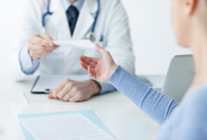 Doctor in Arlington, VA Handing A Patient A Medical Document